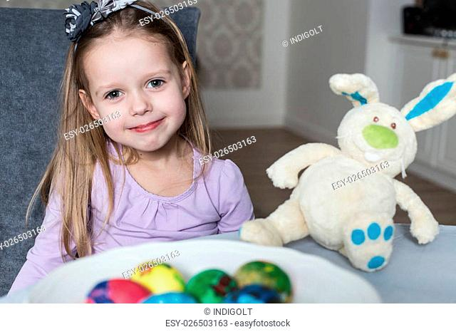 Smiling cute kid with easter eggs and plush bunny. Easter, holiday and child concept