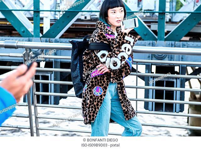 Stylish young woman making smartphone call while strolling on millennium footbridge, London, UK