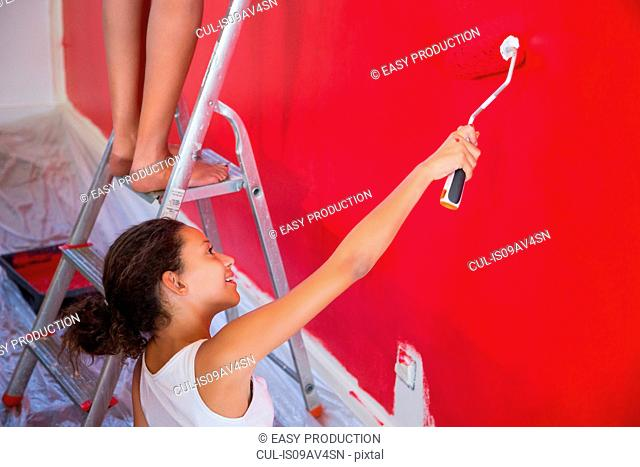 Girl and mother painting red wall with paint roller