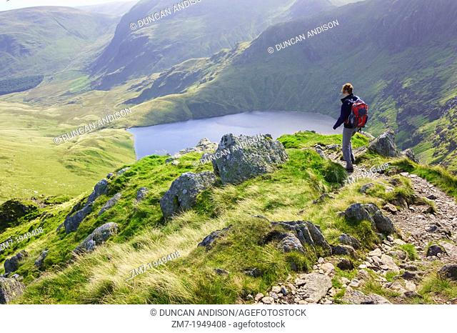 A female hiker walking down Long Stile towards Rough Crag with Blea Water in the distance in the Lake District