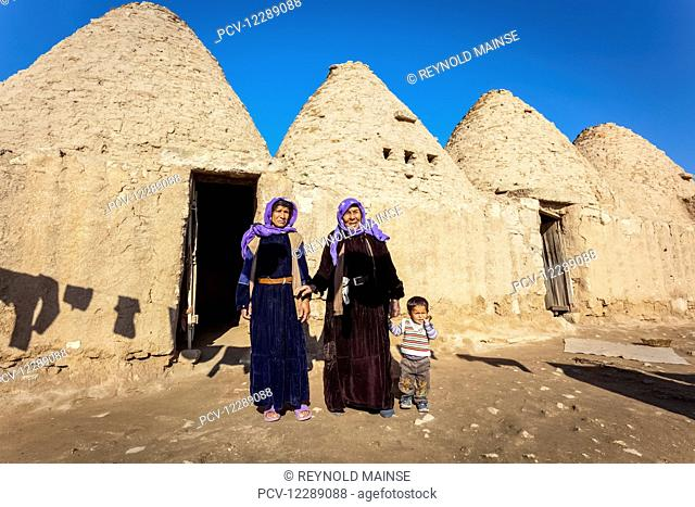 Two women and a child standing outside the doorway of a primitive dwelling; Harran, Turkey