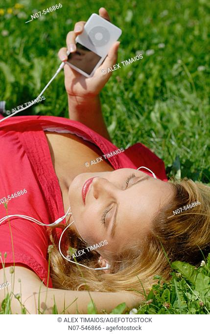 Young girl with a red dress enjoying mp3 music and relaxing