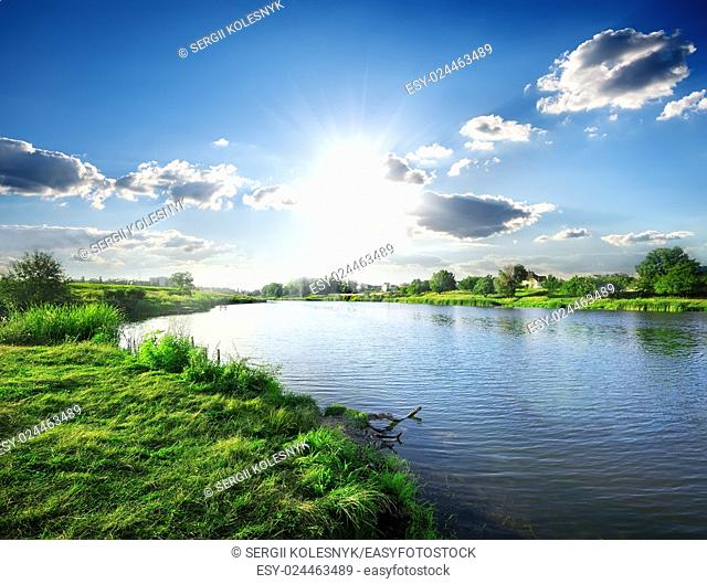 Sun over calm river in the spring morning