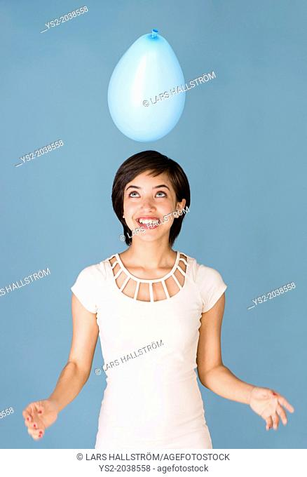Beautiful young multiracial woman having fun with blue balloon at celebration