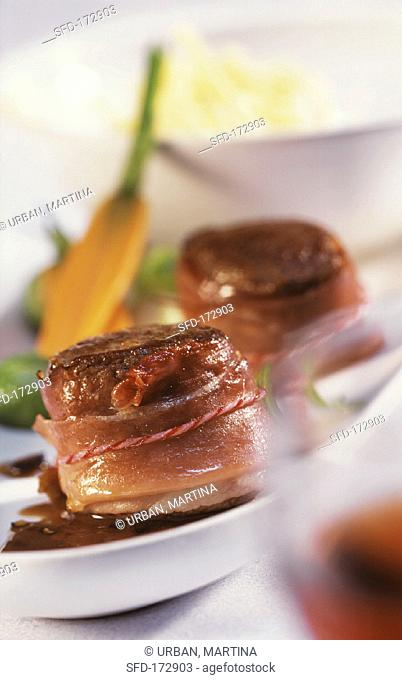 Venison fillet wrapped in bacon on juniper sauce