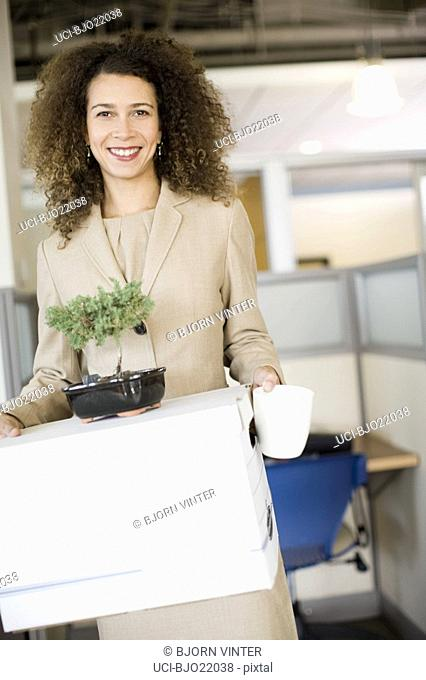 African businesswoman carrying box
