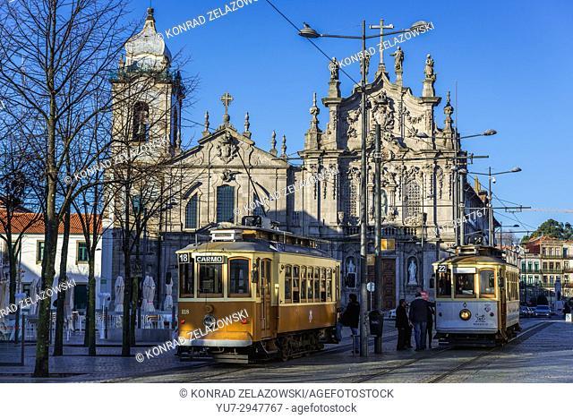 Vintage trams in Vitoria parish of Porto, Portugal. Carmelite Church (Igreja dos Carmelitas Descalcos), Carmo Church (Igreja do Carmo) on background
