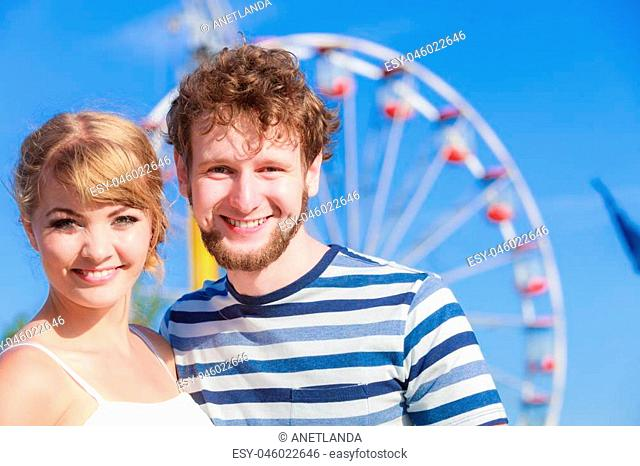 Summer holidays and happiness concept. Young tourists loving couple outdoor in amusement park ferris wheel in the background