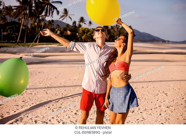 Young couple on beach looking up at balloons, Koh Samui, Thailand