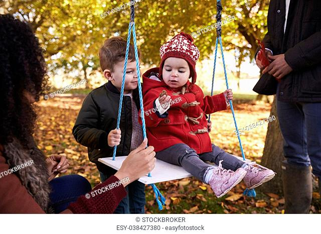 Parents With Children Playing On Tree Swing In Autumn Garden