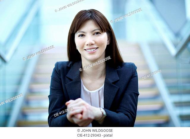 Portrait confident businesswoman sitting on stairs