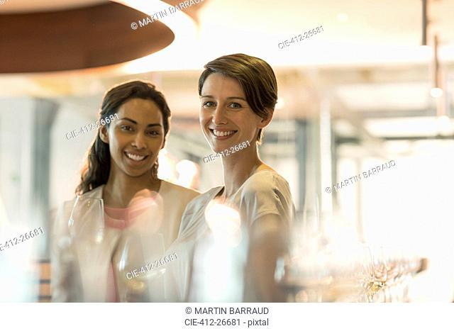 Portrait smiling women wine tasting in winery tasting room