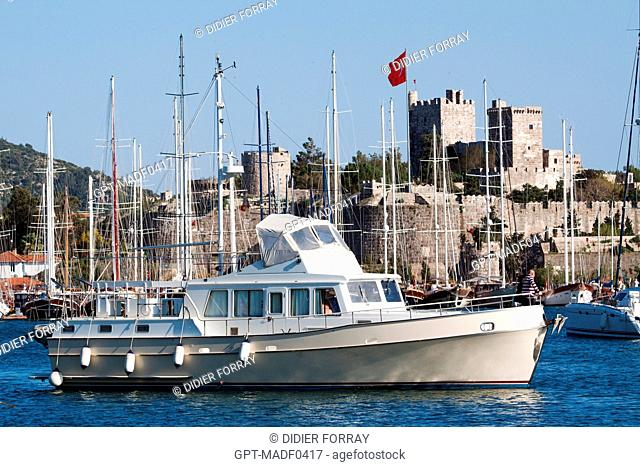 BOAT MOORING IN THE MARINA OF BODRUM AT THE FOOT OF THE FORTIFIED CASTLE OF SAINT PETER 15TH CENTURY, AEGEAN COAST, TURKEY