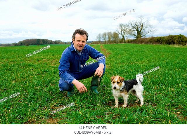 Portrait of farmer crouching in field with dog