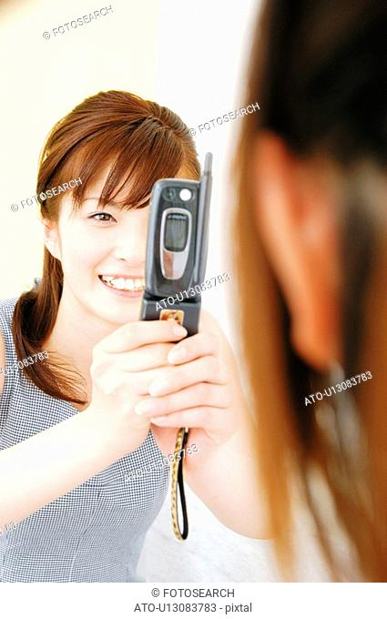 Woman taking a picture with a portable phone