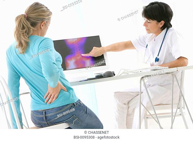 WOMAN CONSULTING FOR BACK PB. Models. On screen, x-ray of the spinal column