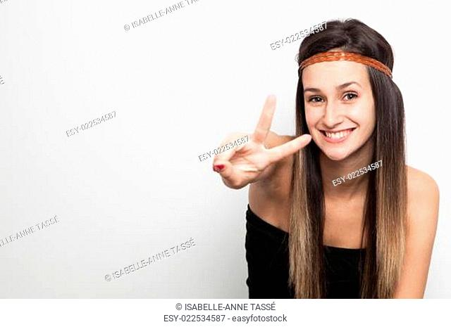 Young woman posing on a white background doing peace