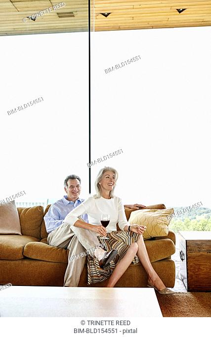 Older Caucasian couple drinking wine on sofa