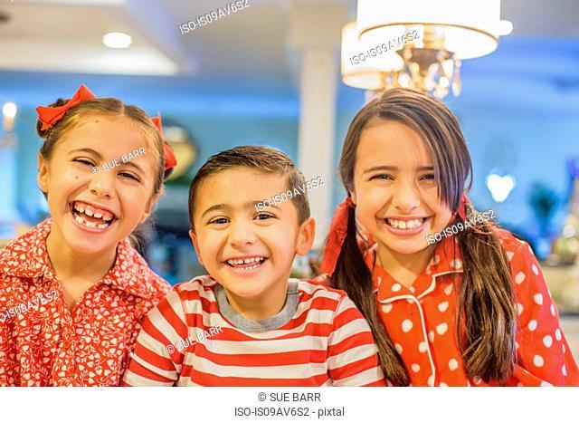 Portrait of children wearing pyjamas looking at camera smiling