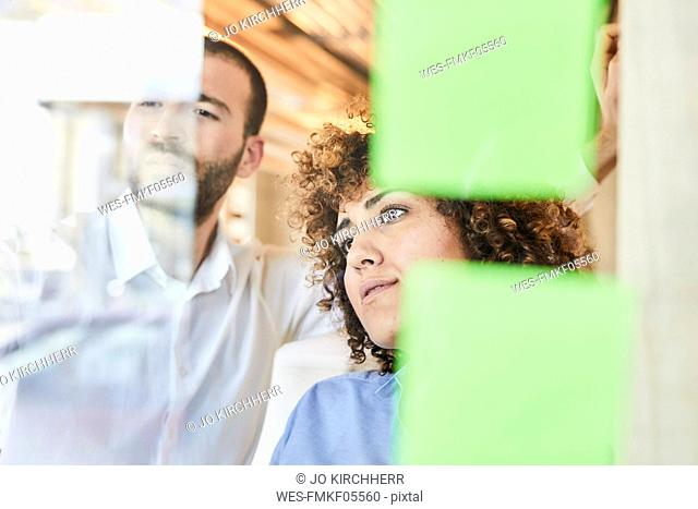 Two colleagues brainstorming with post-its on glass pane