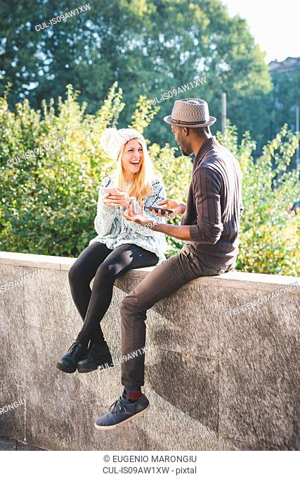 Couple chatting and using smartphone on top of cement wall