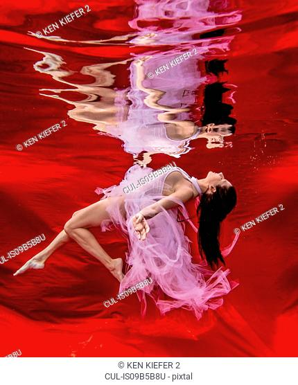 Underwater view of poised woman with flowing pink dress against red background