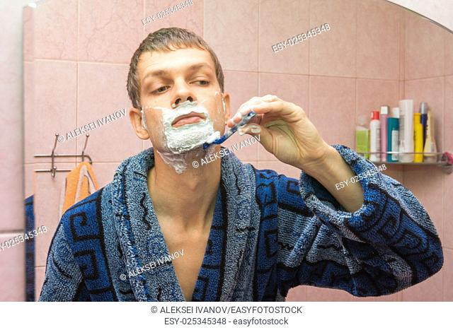 Young guy shaves neck in front of the mirror