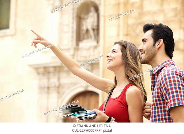 Smiling young woman pointing out sights