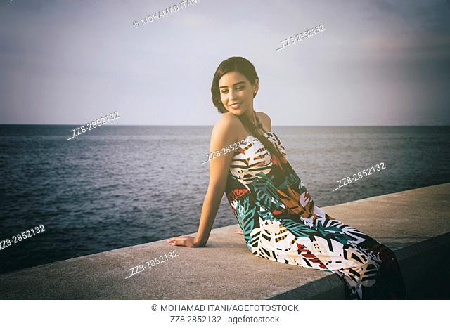 Happy young woman sat by the sea smiling