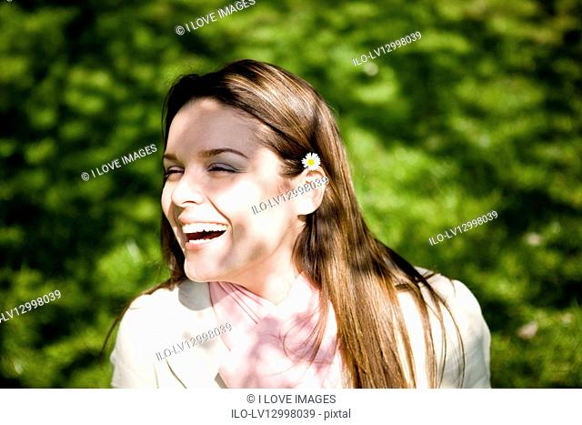 Portrait of a young woman with a daisy in her hair, laughing