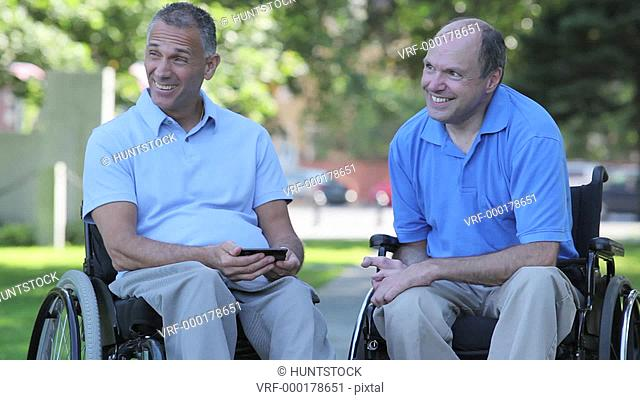 Two men in wheelchairs in park using a smartphone one with spinal cord injury and one with Friedreich's Ataxia