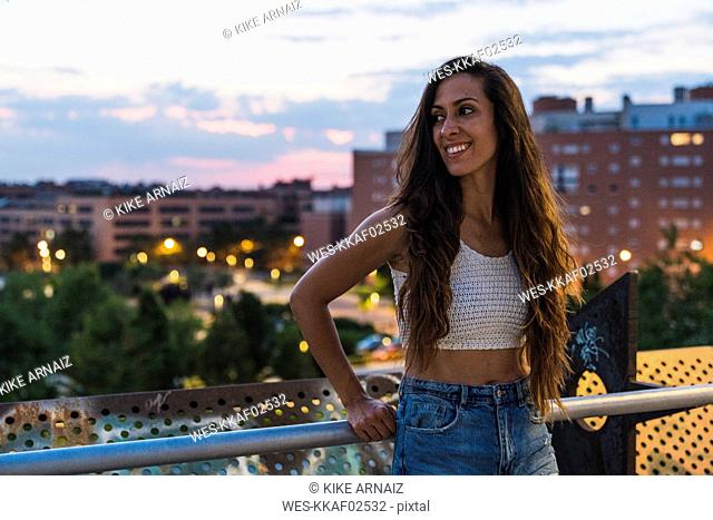 Beautiful smiling young woman with long brown hair in the city at dusk