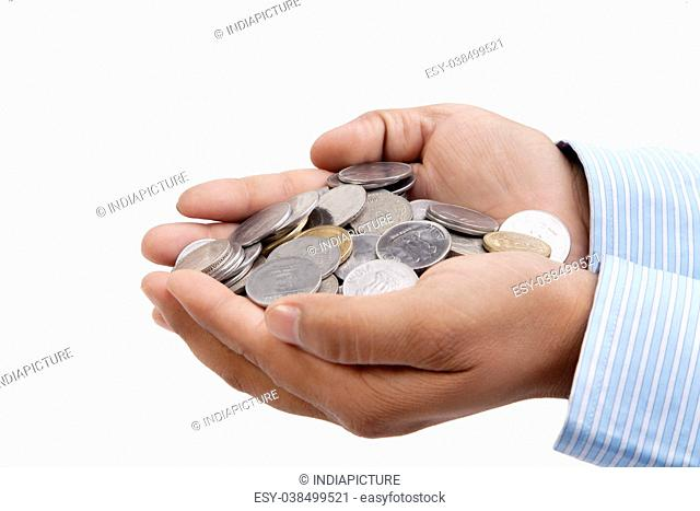 Handful of coins in palm hands isolated on white