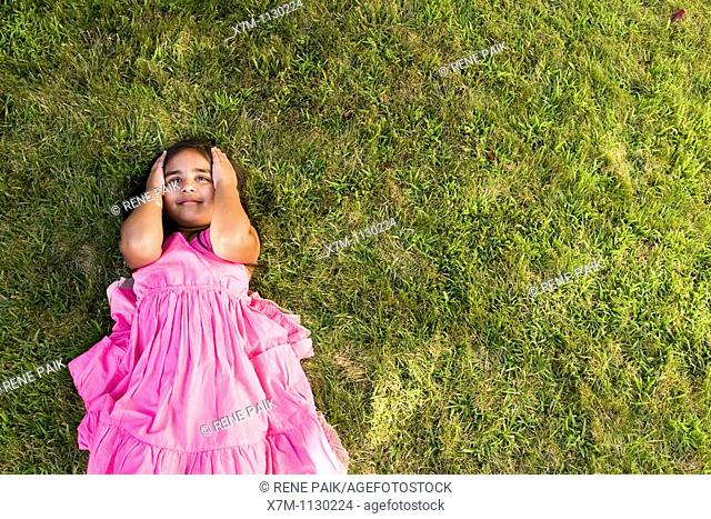 A little Indian girl thinking while laying on green grass