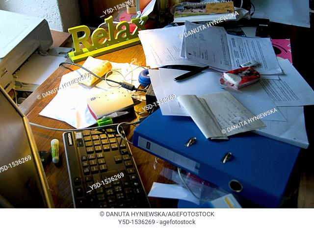 mess on the desk with 'relax' sign