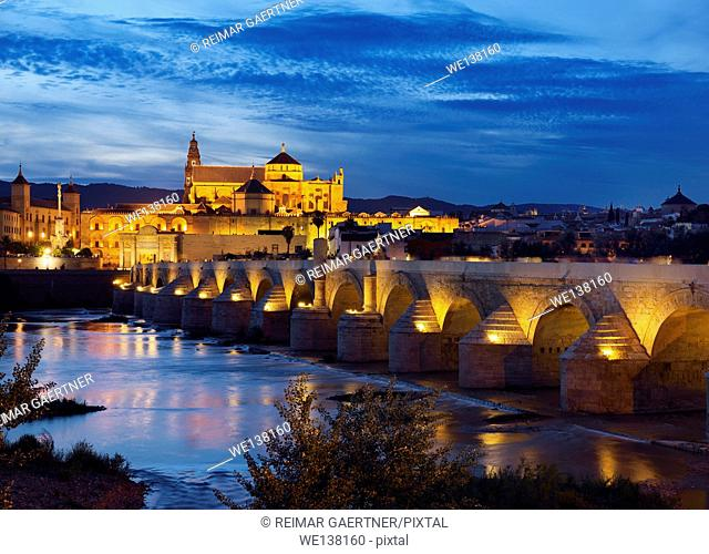Roman Bridge over the Guadalquivir River with Episcopal Palace and Cordoba Cathedral at dusk