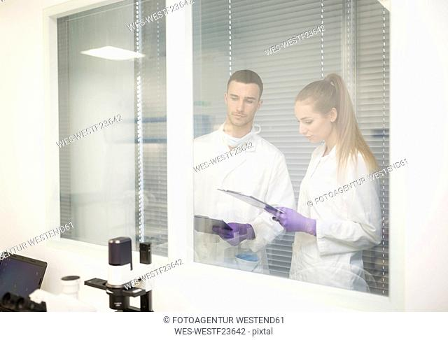 Man and woman in lab coats with clipboards behind glass pane