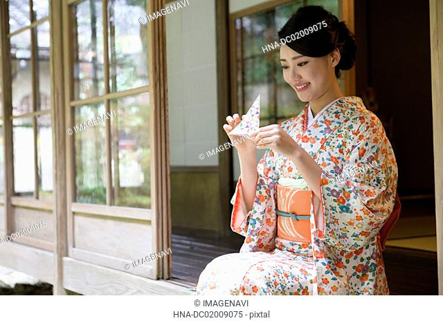 Young Japanese woman in kimono doing Origami