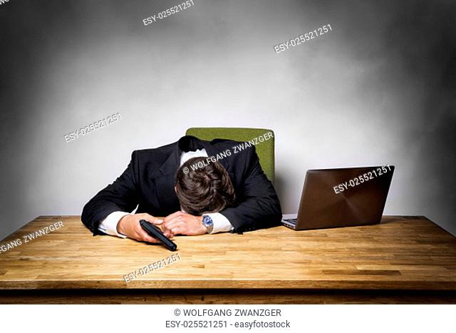 Overworked businessman in office with gun