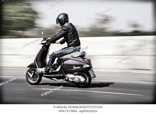 Man with motorcycle, speed circulating around town