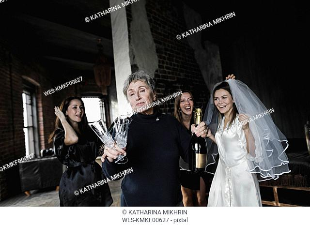 Bride's mother, bridesmaids and bride drinking champagne together