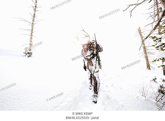 Caucasian woman hunting in forest carrying antlers