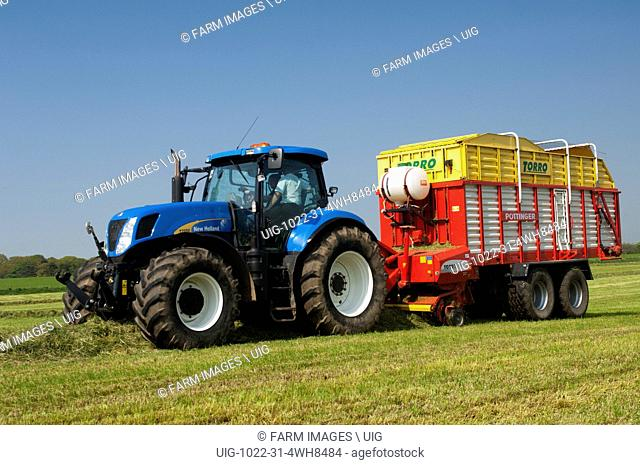 Picking up grass in meadow using a Pottinger forage wagon and New Holland tractor. Northumberland, UK. (Photo by: Wayne Hutchinson/Farm Images/UIG)