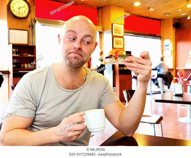 Middle-aged man enjoying coffee with a pintxo in a cafe