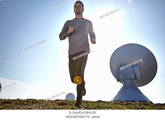 Germany, Raisting, young man jogging at ground station