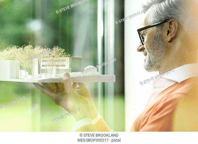 Happy man looking at architectural model