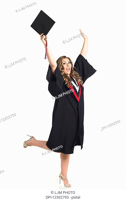Young woman holding her hands up in celebration of her graduation; Edmonton, Alberta, Canada