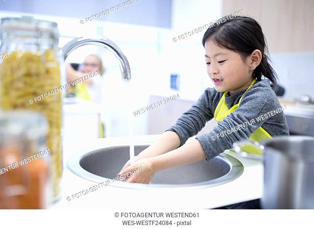 Schoolgirl washing her hands in cooking class