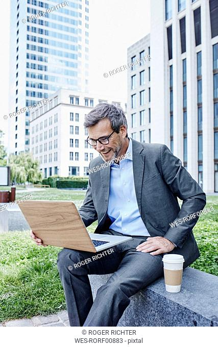 Happy mature businessman outdoors with laptop and takeaway coffee