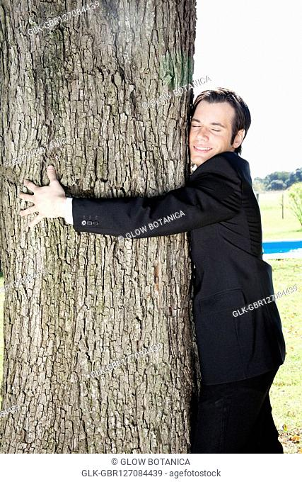 Businessman hugging a tree and smiling